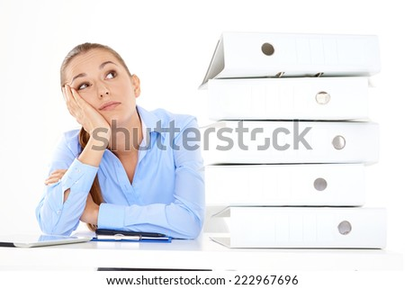 Bored female employee with a lot of work left to do on white background - stock photo