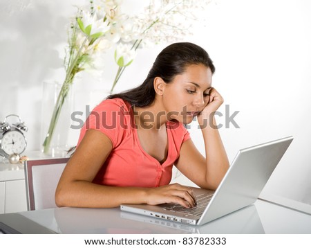 bored girl with laptop homeworking - stock photo