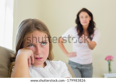 Bored girl with mother scolding her in background at home - stock photo