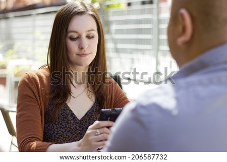 bored incompatible couple on an outdoor date outdoors - stock photo