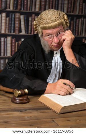 Bored judge with authentic court wig and gavel in court - stock photo