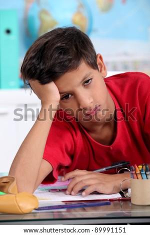 Bored little boy in classroom - stock photo