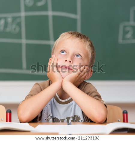 Bored little boy in school sitting at his desk in front of the blackboard staring dreamily up into the air with his chin on his hands - stock photo