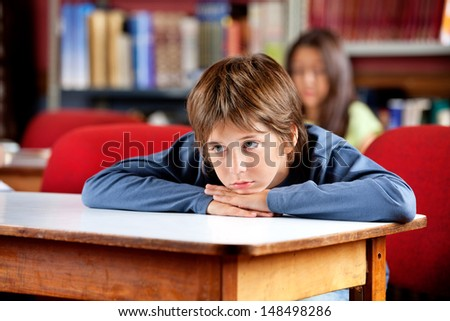 Bored little schoolboy looking away while leaning on table in library with female classmate in background - stock photo