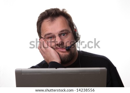 Bored looking 30-something computer operator on white background wearing phone headset