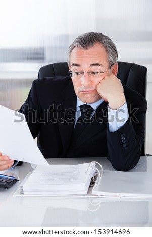 Bored Mature Businessman While Calculating At Desk - stock photo