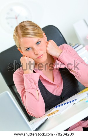Bored modern business woman sitting at office desk and keep head on hands - stock photo