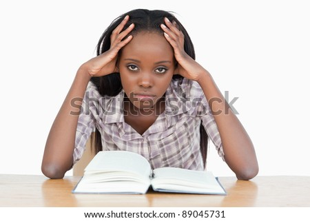 Bored student trying to read a book against a white background - stock photo