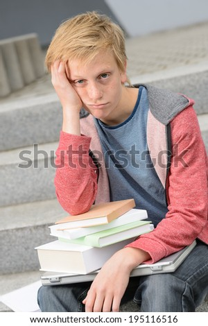 Bored student with books and laptop sitting outside on steps