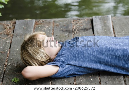 Bored teen laying back and relaxing on the dock - stock photo