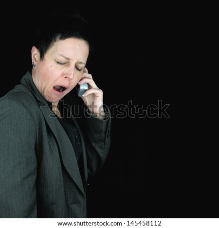bored, tired businesswoman yawning during telephone conversation, against black background - stock photo