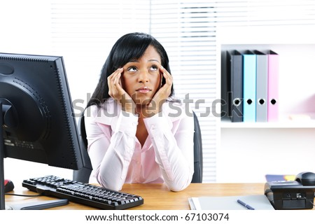 Bored unhappy young black business woman at desk in office - stock photo