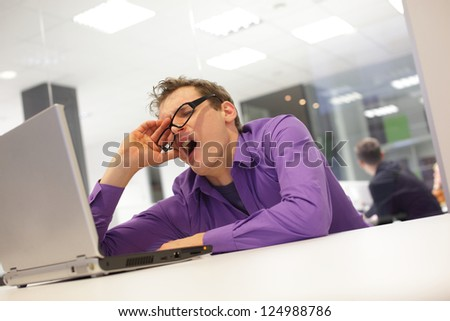 bored yawning businessman working with laptop supporting his head on his hand in office space - stock photo