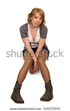 Bored young blonde girl sitting facing the camera with her hands dangling down beween her legs isolated on white - stock photo