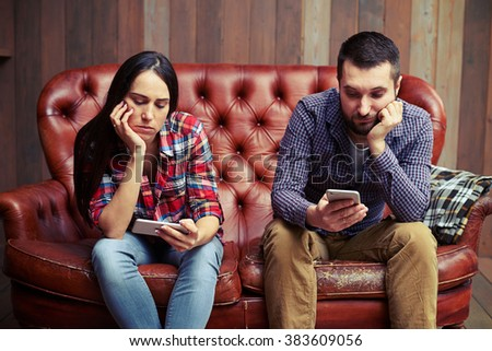 bored young couple sitting on couch and looking at their phones - stock photo