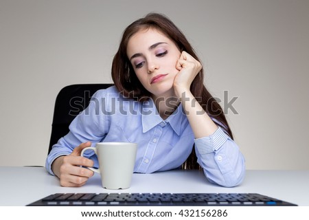 Bored young female looking into coffee cup at desk with computer keyboard