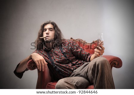 Bored young man sitting on an armchair and holding a glass of champagne and smoking a cigar