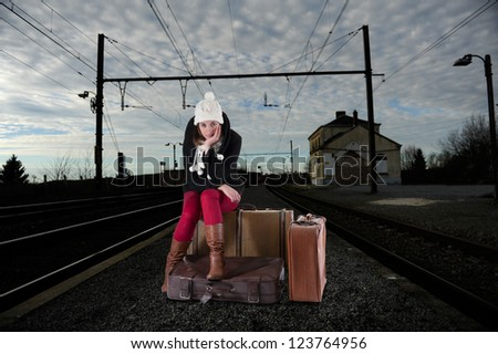 bored young woman waiting for her train - stock photo