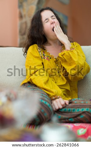 Bored young woman yawning her head off at home - stock photo