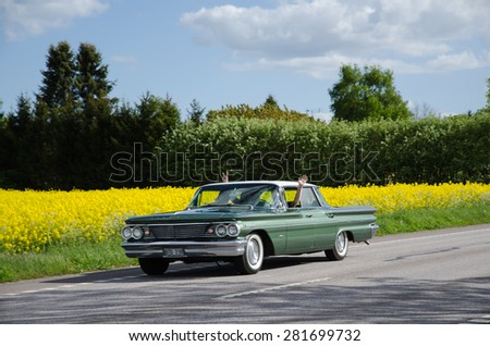 BORGHOLM, SWEDEN - MAY 23, 2015: Old timer car Pontiac Bonneville, 1960, on the road heading for a car meeting in the town of Borgholm in Sweden, Photo is taken on May 23, 2015, at Oland in Sweden. - stock photo