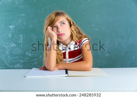 Boring sad expression student schoolgirl on classroom desk at school green chalk board - stock photo