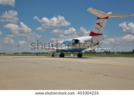 Borispol, Ukraine - July 5, 2014: Austrian Airlines Fokker-70 passenger plane taxiing to the terminal after landing - rear view - stock photo