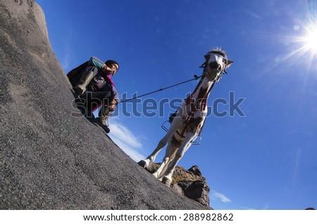 BORMO - JUNE 13, 2015: Horsemen having a cigarette brake  at The Tengger Sand Sea, Bromo Indonesia - stock photo