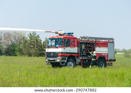 BORYSPIL, UKRAINE - MAY, 20, 2015: Fire-brigade on Fire Engine Mercedes using a water cannon during a training event at Boryspil International Airport, Kiev, Ukraine - stock photo