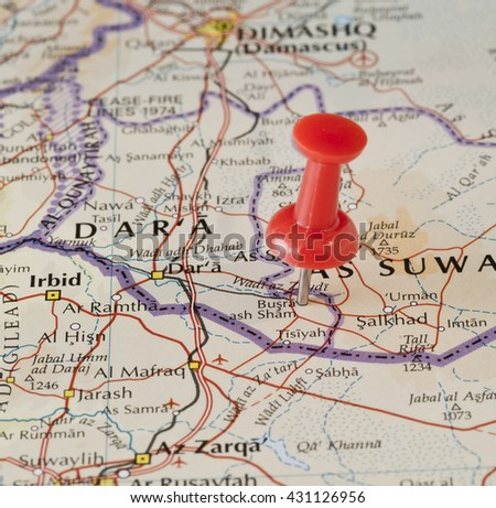 Bosra (Busra) marked on map with red pushpin. Selective focus on the word Busra and the pushpin. Pin is in an angle. Midground is sharp while foreground and background is blurry. - stock photo