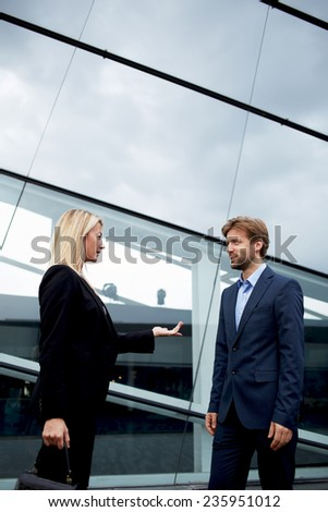 Boss and employee standing outside the office talking serious, confident businesswoman discussing with employee outside the office, business people standing near office building talking about the work - stock photo