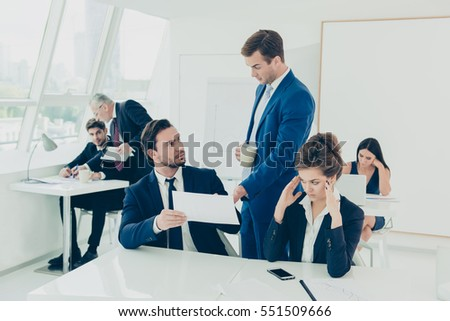 Boss checking financial plan of team of young managers