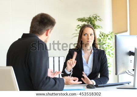Boss denying something saying no with a finger gesture to an upset employee in her office - stock photo