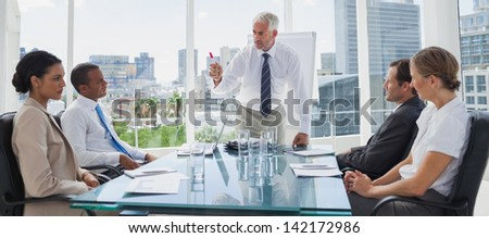 Boss gesturing in front of colleagues during a meeting - stock photo