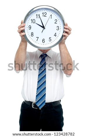 Boss holding a clock in front of his face. Get ready for the meeting in five minutes! - stock photo