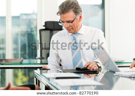 Boss in his office checking mails - stock photo