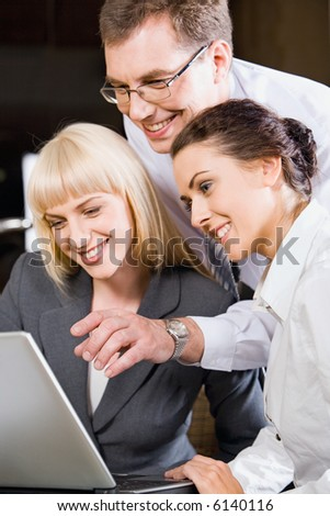 Boss is explaining the correct way of analysis to his colleagues in  the office pointing at the monitor - stock photo