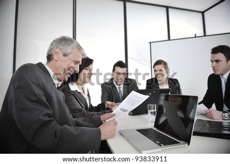Boss reading report at business meeting