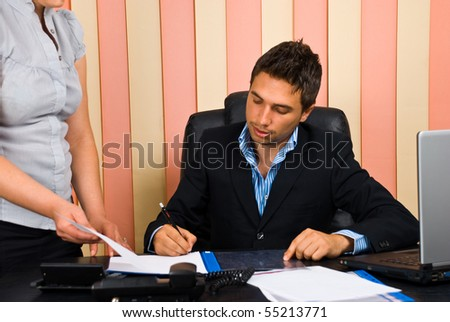 Boss sitting on chair in office signing  his secretary documents - stock photo