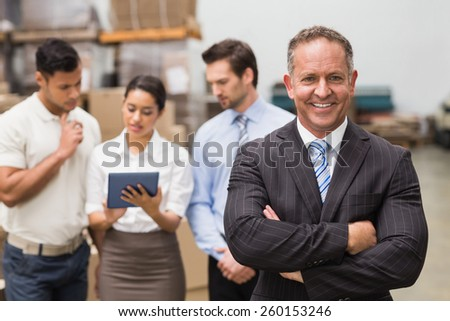 Boss standing with arms crossed in front of his employees in a large warehouse - stock photo