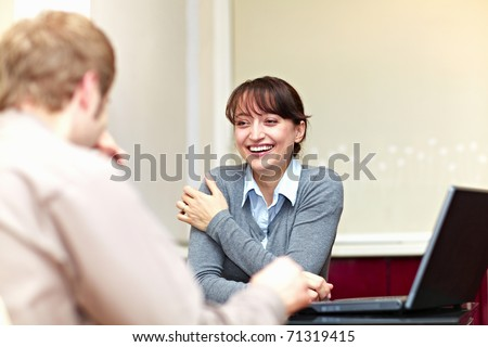 Boss talking to his employee and she is smiling - stock photo