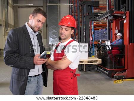 boss talking to worker in uniform in factory - stock photo