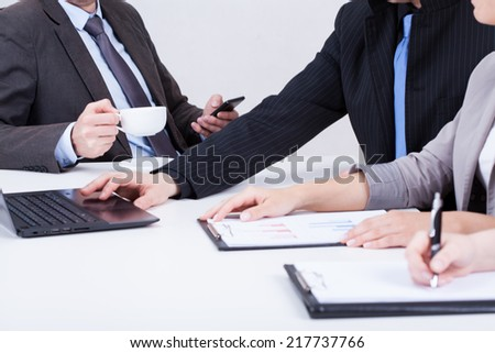 Boss using phone and drinking coffee on business meeting