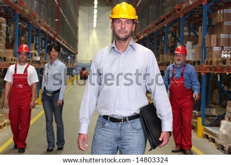 boss with briefcase at the front of team of workforce in warehouse -3 workers in background - stock photo