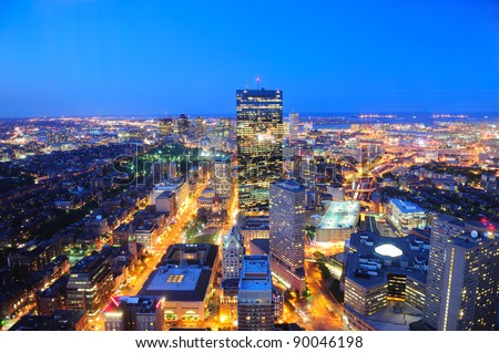 Boston aerial view with skyscrapers at dusk with city skyline illuminated.