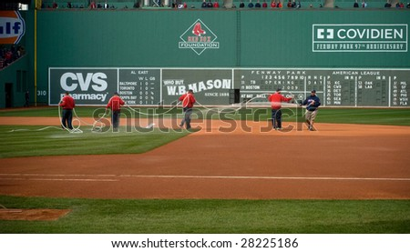 BOSTON - APRIL 7: Ground crews prepare the field for gametime at the Boston Red Sox Opening Day at Fenway Park April 7, 2009 in Boston, Massachusetts. - stock photo