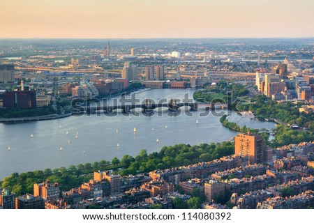 Boston Charles River sunset aerial view with urban buildings and bridge.