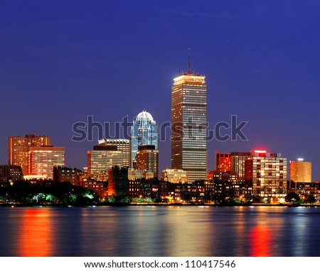 Boston city skyline at dusk with Prudential Tower and urban skyscrapers over Charles River with lights and reflections. - stock photo