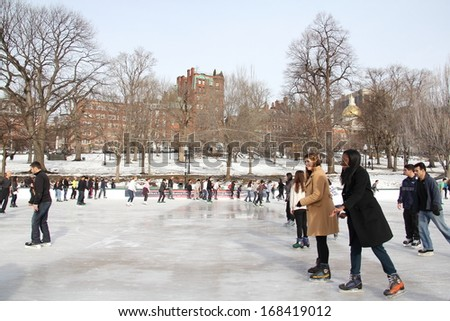 BOSTON - DEC 21: Ice-skating people with white Christmas in Frog Pond at Boston Common on December 21, 2013 in Boston, Massachusetts - stock photo