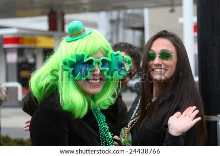 BOSTON, MASSACHUSETTS - MARCH 16: A pair of young women wear festive green glasses during a Saint Patrick's day parade. One woman (left) also wears a funny green wig. The parade was held March 16, 2008 in Boston, Massachusetts. - stock photo