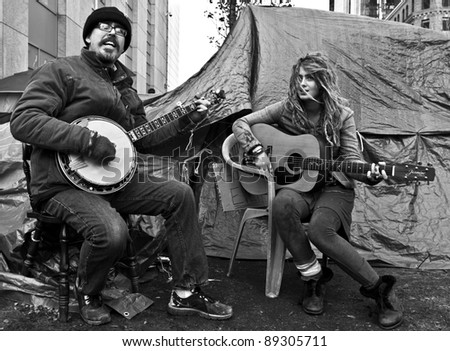 BOSTON, MASSACHUSETTS - NOVEMBER 19: Two members of the Occupy Boston protest sing to the people in its camp in Boston, Massachusetts, USA on November 19, 2011.